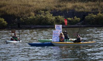 A group of individuals on kayaks on Cayuga Lake hoist their signs in the air to protest the expansion of the Cargill Salt Mine.