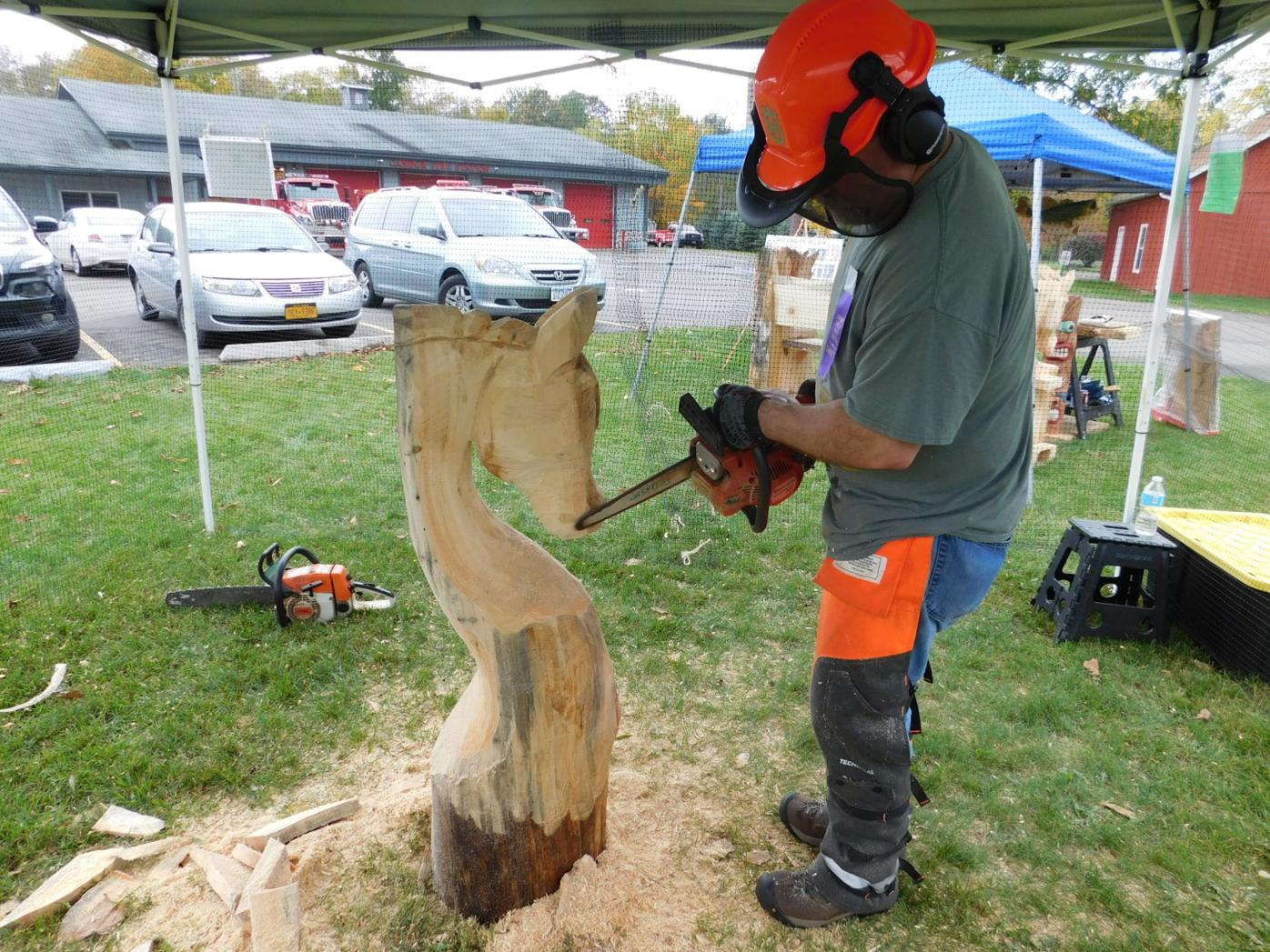 David Westgate uses a special chain saw designed for woodworking to carve a horse head at the Woodcarvers' Show