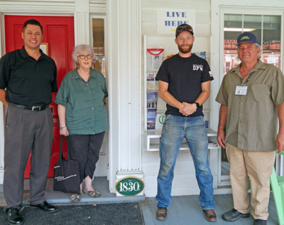 """Trumansburg Mayor Rordan Hart, Village Code Enforcement Officer Tom Myers, Village Department of Public Works Supervisor Dustin Vanderzee and Trumansburg Village Historian S.K. List hang a sign with the year the Village Hall was built as part of """"The Plaque Project"""" July 19."""