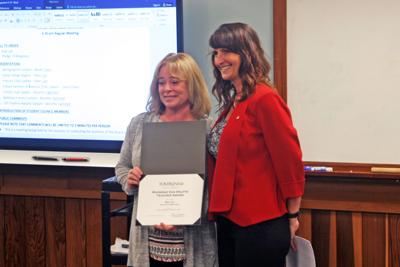 Babs Car (left), Groton schools business teacher, receives the Raymond Van Houtte Teacher Award from Deborah Hoover, Vice President, Officer and Branch Manager at Tompkins Trust Company, at a Board of Education meeting on June 3.