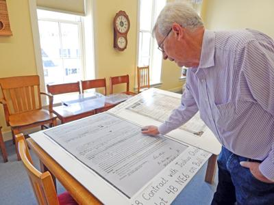 Alan Chaffee, Newfield Town Historian, points out some interesting aspects of a 1828 Newfield land contract, blown up far larger than its original size. Documents like these will be available for viewing at a new Newfield History Center on Main Street.