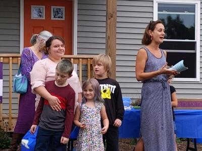 Tamrie Oliver stands with her three children while Liz Warner talks at the celebration for the completion of the house.