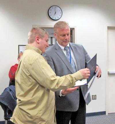 Fred Boudreaux beams with pride as Candor Central School District Superintendent Jeff Kisloski presents him with his diploma.