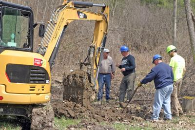 Several construction workers search for the source of the water system for the house located on 1932 Slaterville Rd.