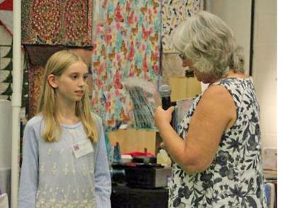Cyndi Slothower (right) of Quilters Corner in Ithaca presents the Nina Linton award to Elin Kopelson at the 2017 Tompkins County Quilters Guild Quilt Show. The award recognizes a standout beginner quilter.