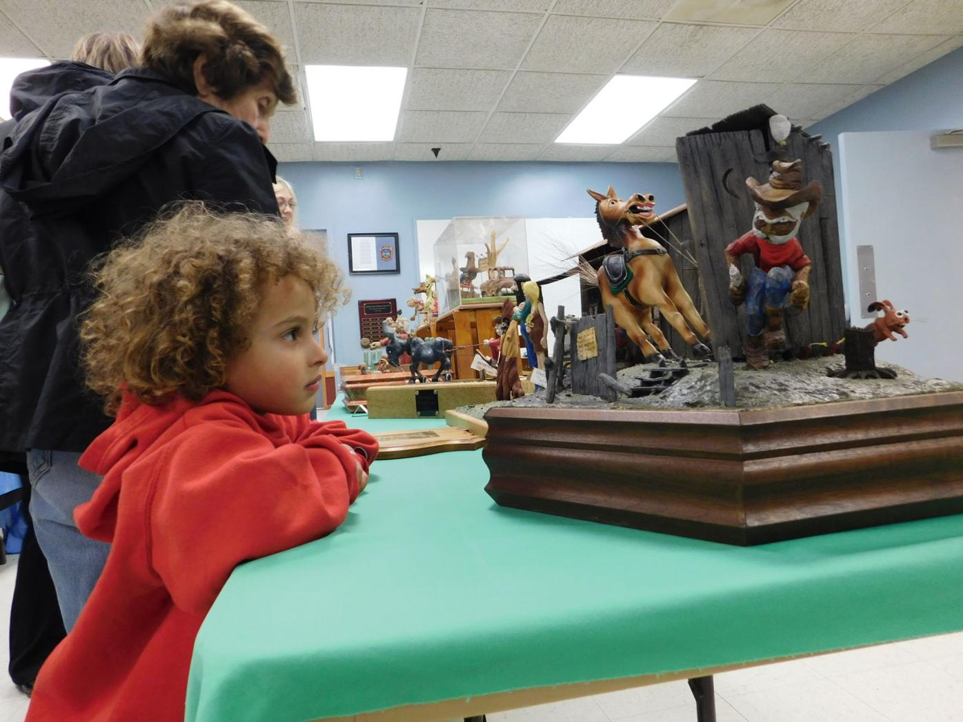 Orion Halton, 4, of Brooktendle, admires a woodcarving at the Candor Fall Festival