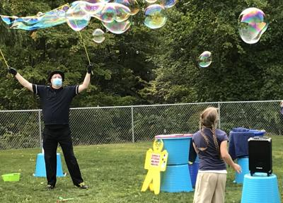 Rayna Gingerich (bottom right) and performer Doug Rougeux (left of center) play with bubbles at the library's summer reading program celebration.
