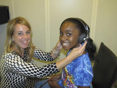 Audiologist Monica Brace with a young client