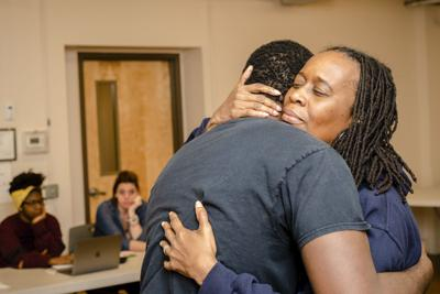 Two members of the Re-Entry Theatre program embrace during a recent rehearsal.
