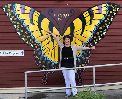 Kathy Connell posses in front of her mural that hangs on the side wall of the Dryden Hotel Building.