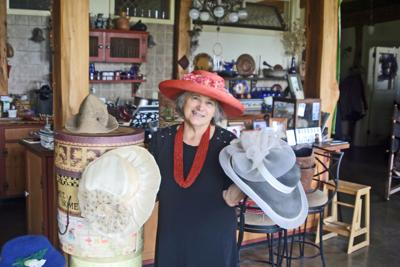 Lansing Town Councilwoman Andra Benson wears and holds a few pairs of hats from her collection.