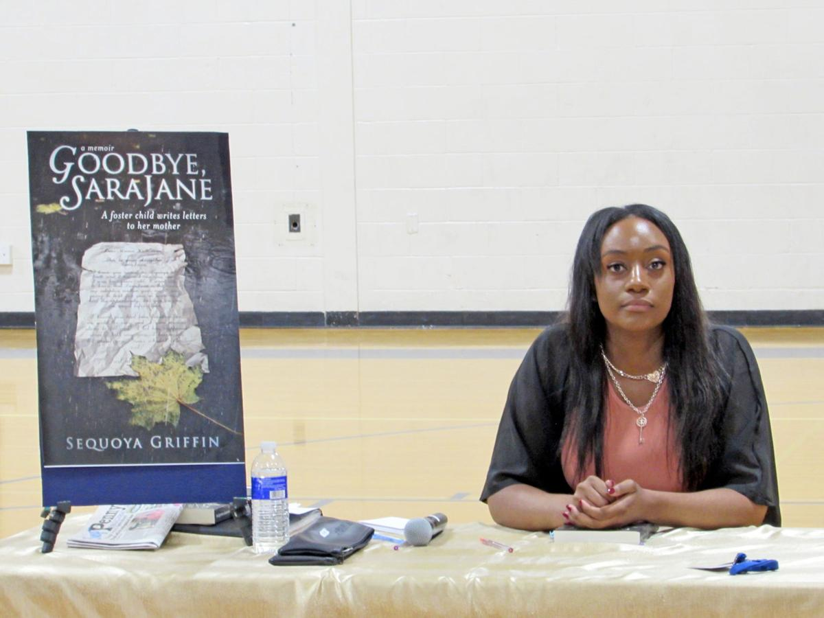 """Sequoya Griffin by an enlarged version of her memoir, """"Goodbye Sara Jane.""""The book signing was held in the Candor High School gym."""