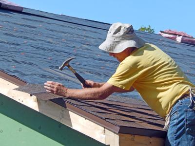 Eric Kurtz, a member of the Dryden Rotary Club, hammers in a shingle on top of the roof of one of the new houses that is being built on 1932 Slaterville Road on Aug. 31.