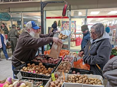 A vendor pours potatoes into a bag for a customer at the winter market on Jan. 4.