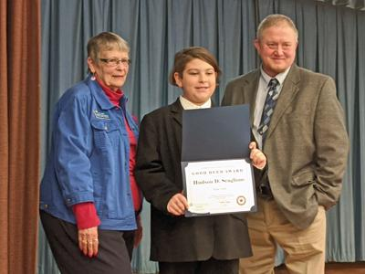 Hudson Scaglione (center) holds his award with Betty Conger (left) and Principal Kent Maslin (right) standing by his sides.