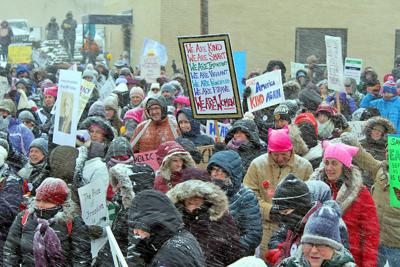 Participants in the Women March in Seneca Falls hold up signs during the on event Jan. 18.