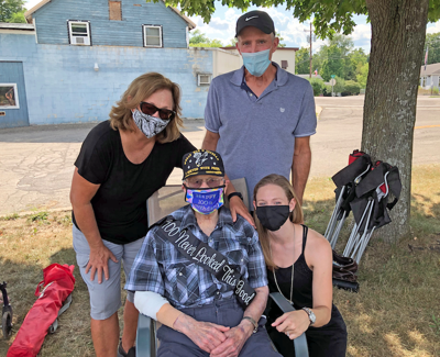 Robert Stein at his 100th birthday parade with his daughter and son-in-law, Bobbi and Don Brock, and his granddaughter, Tricia Guba.