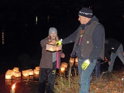 Elise Sorensen is handed a lantern by Scott Goodrich, a Second Wind Cottages resident, at Second Wind's first Lantern Festival at the Cherry Arts in Ithaca Nov. 10.