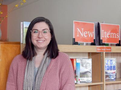 Danielle Perkins, the new director of the Newfield Public Library, stands in front of the new releases. Perkins started in her role as director in February.