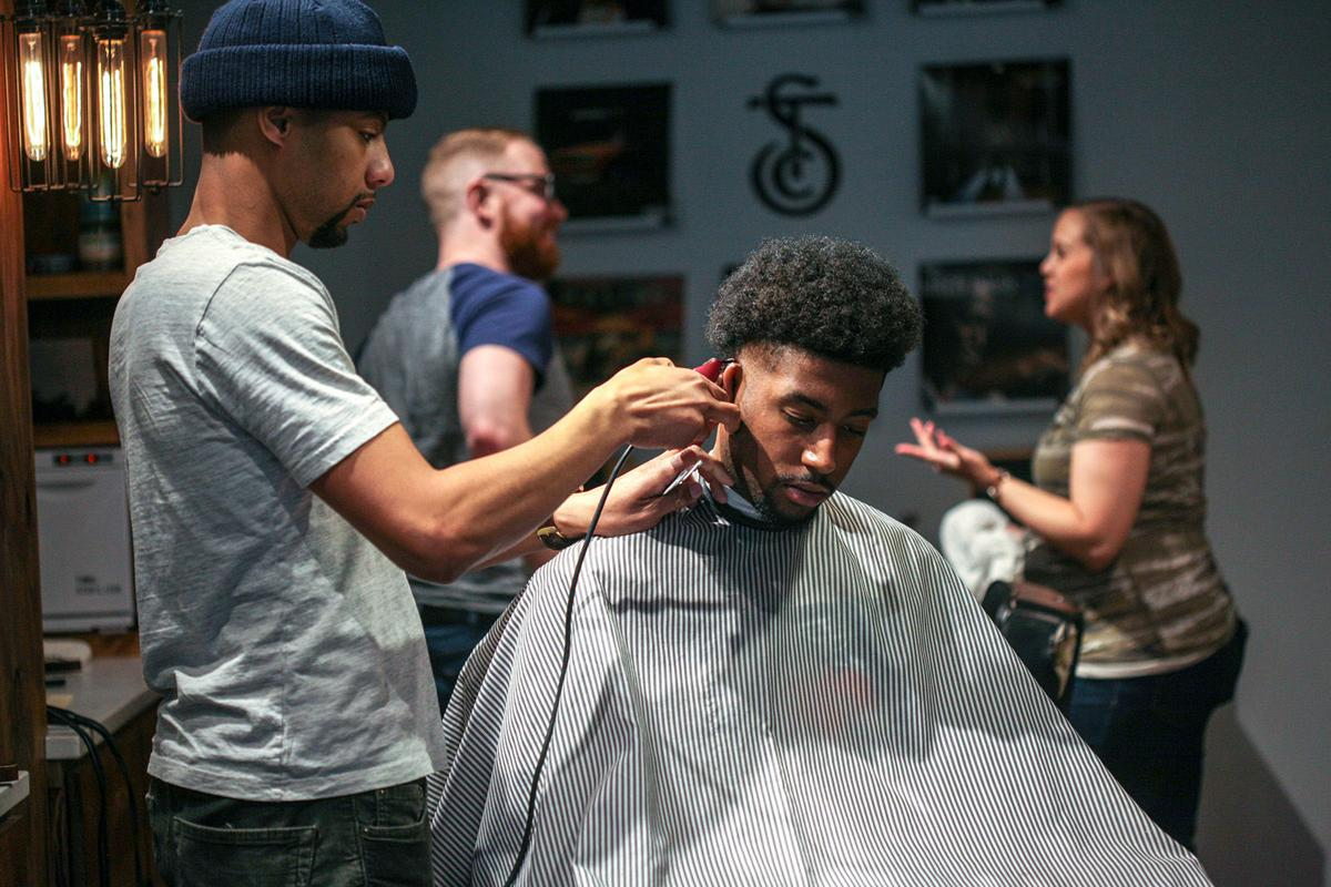 Lonell Carr, 28, of Oak Park, left, cuts Willie Garwood's hair, 23, of Detroit, at the Social Club Grooming Company on the Wayne State University campus in Detroit, Mich. on Friday, Jan. 11, 2019. Sebastian Jackson, co-owner, says he wanted to preserve the safe space for dialogue known in a black barbershop, but also have different races of barbers to expand the dialogue.