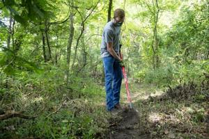 Student working to restore old swamp trail on MSSU campus