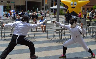 Members of the Lincoln Fencing Club give a demonstration at Tower Square
