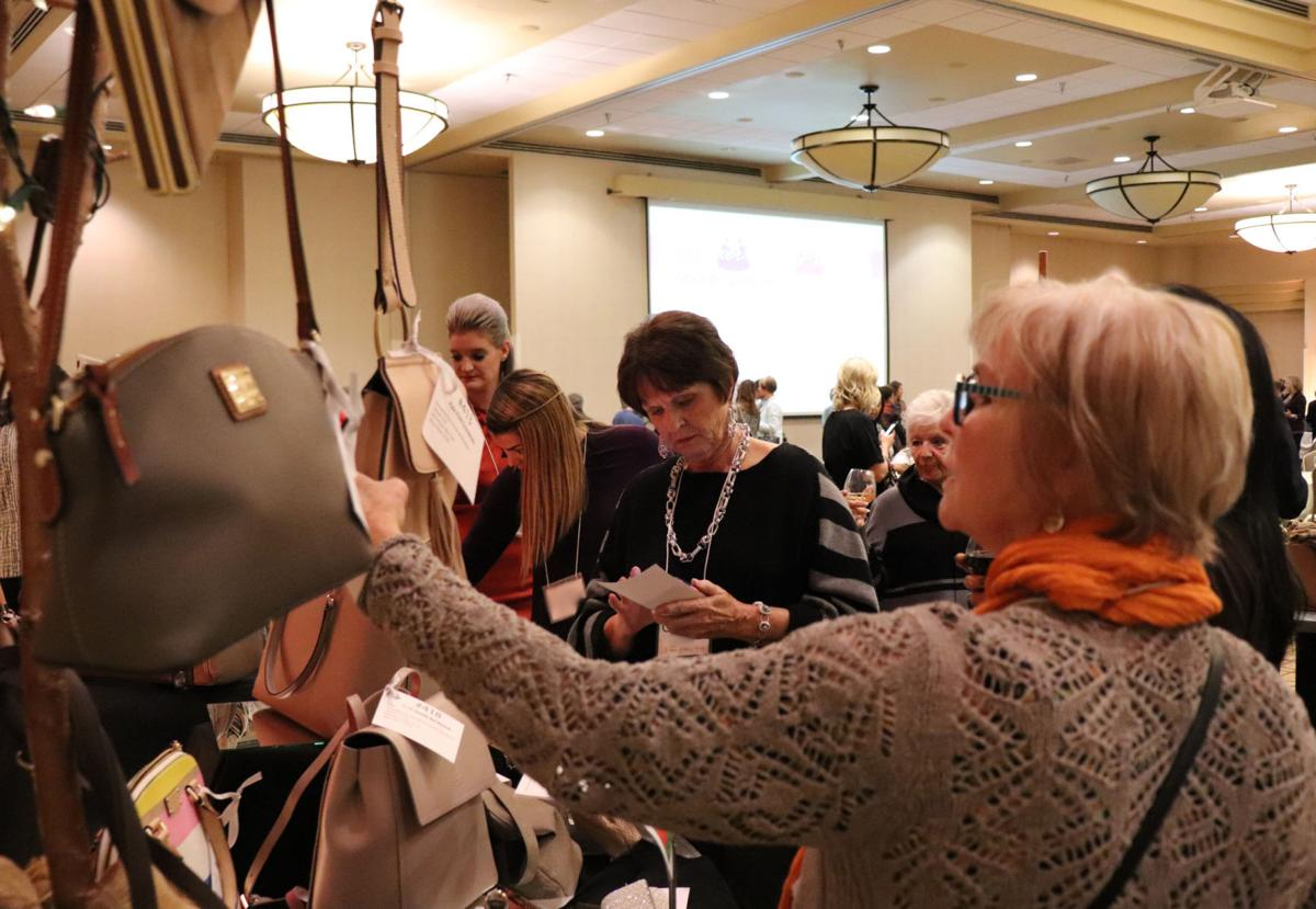 Guests comtemplate bidding on one-of-a-kind and designer handbags