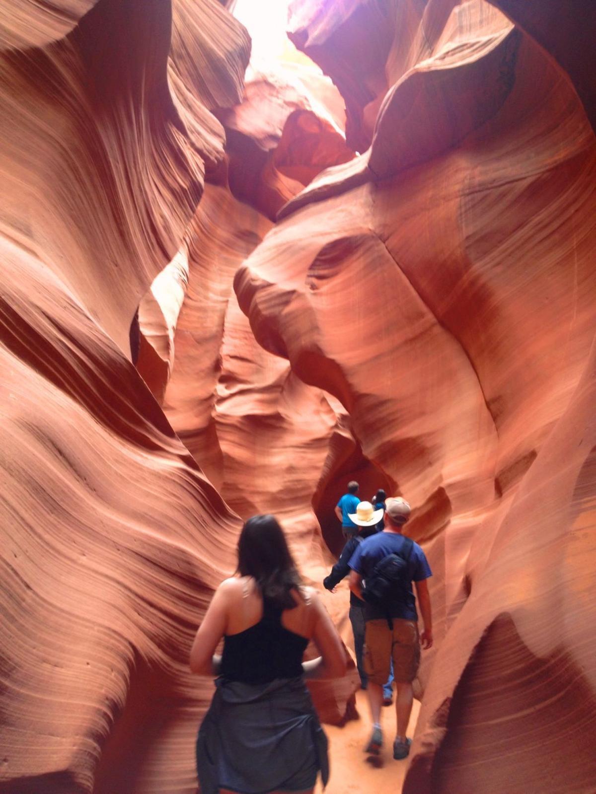 Tourists walk through a narrow passageway