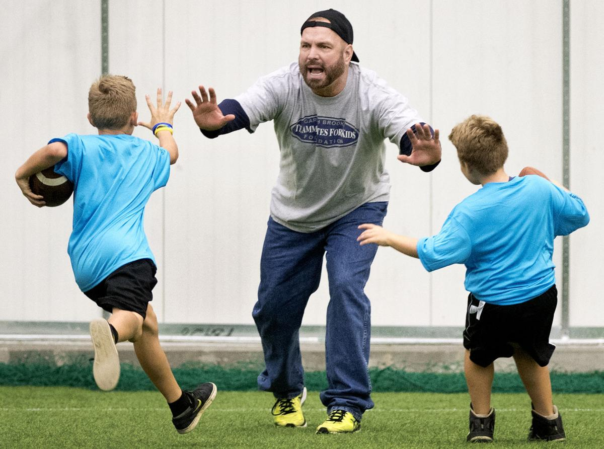 6903c0551a7 Youth participating in the Garth Brooks Teammates Football ProCamp race to  the man himself (center) as they compete in a relay race Saturday at  Speedway ...