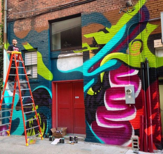 Pacheco works on mural at Kiechel