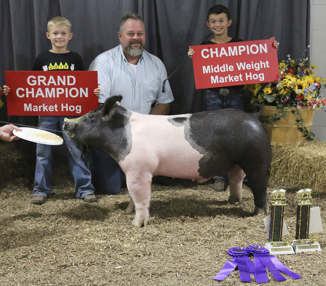 Swine Show champions Izek and Michael Lockee with judge Wade Hilker