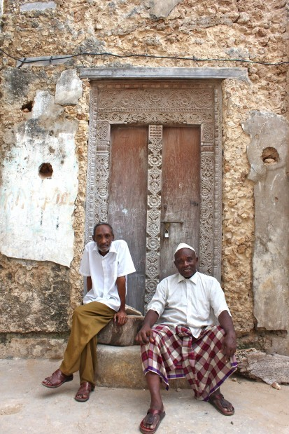 Local residents seated in front of an ornate, Lamu-style door