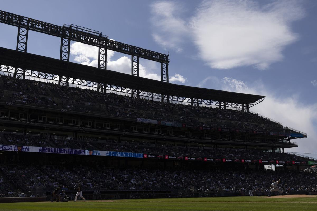 Starting pitcher Julio Urias #7 of the Los Angeles Dodgers delivers to home plate against Elias Diaz #35 of the Colorado Rockies during the seventh inning at Coors Field on April 4, 2021 in Denver, Colorado.