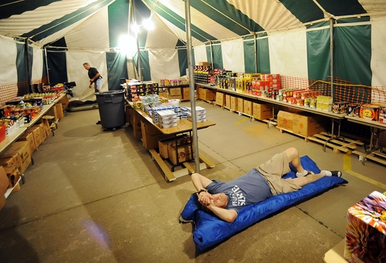 Jim  Woody  Woodson (laying down) and Eric Schoen guard the fireworks tent in the Southview Christian Church parking lot in Lincoln on Thursday night. & Guarding against fireworks thieves | Local | journalstar.com
