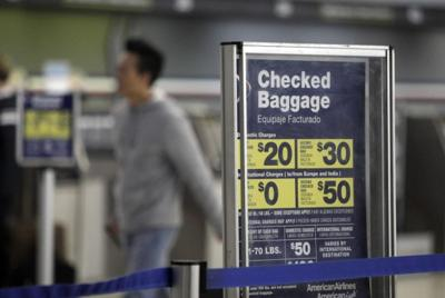 A traveler walks past a sign displaying fees checked baggage fees on American  Airlines flights at Lambert St. Louis International Airport in St. Louis in  ... 480cb07fedb50