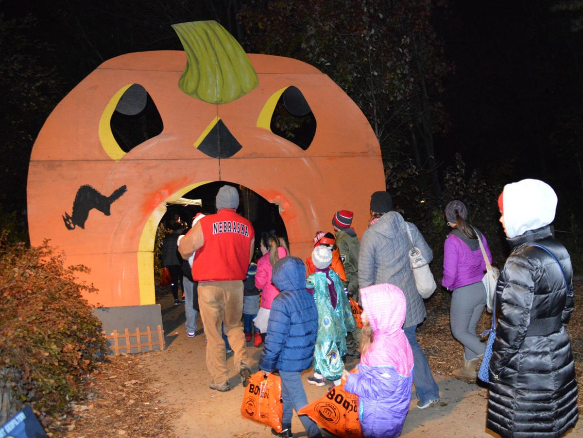 Attendees walk through a jack-o-lantern's mouth
