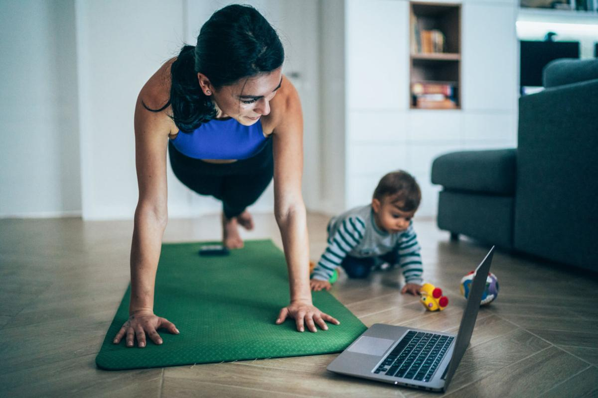 A mom works out at home to an online class