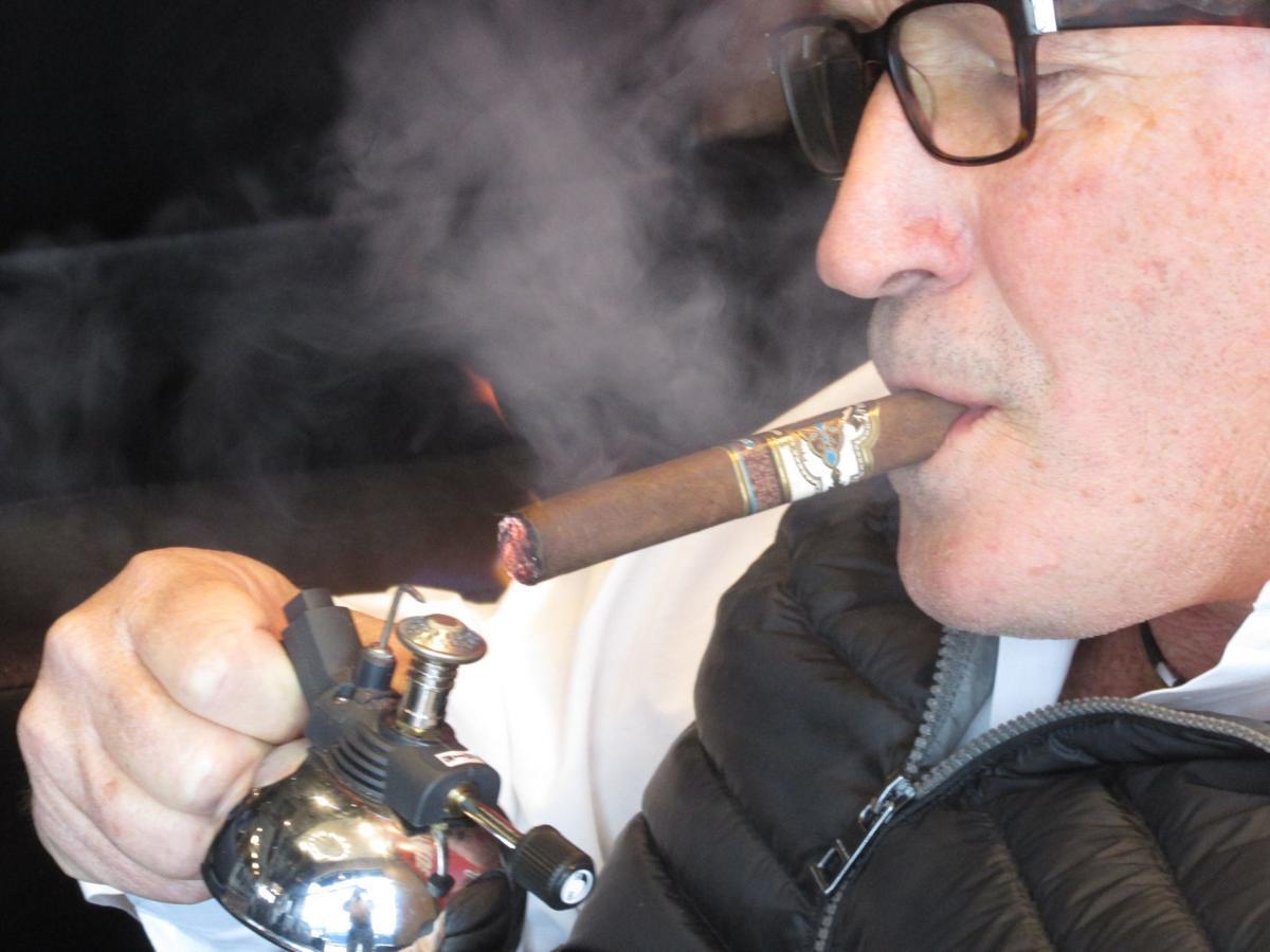Alan Rubin lights up one of his cigars