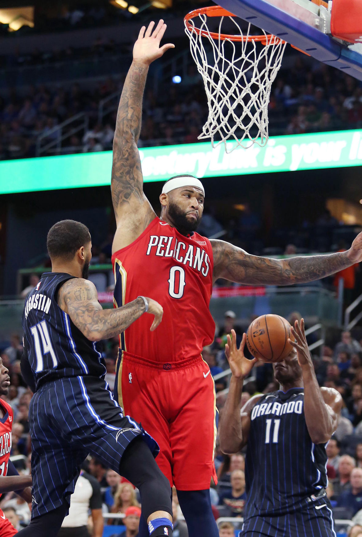 The New Orleans Pelicans' DeMarcus Cousins (0) leaps over the Orlando Magic's D.J. Augustin (14) and Bismack Biyombo (11) at the Amway Center in Orlando, Fla., on December 22, 2017.