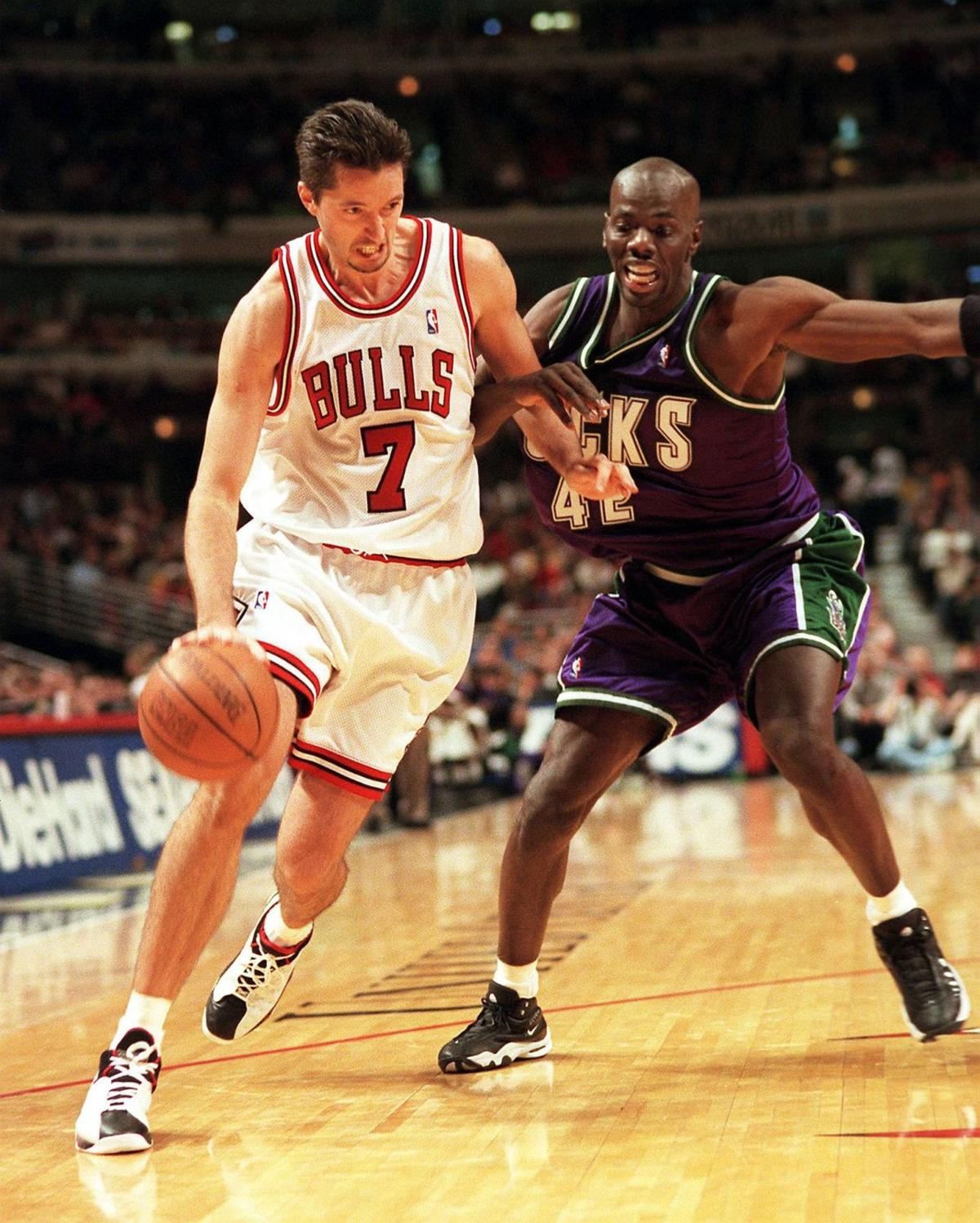 Bulls forward Toni Kukoc drives to the basket against the Bucks' Tyrone Hill at the United Center on Feb. 23, 1999.