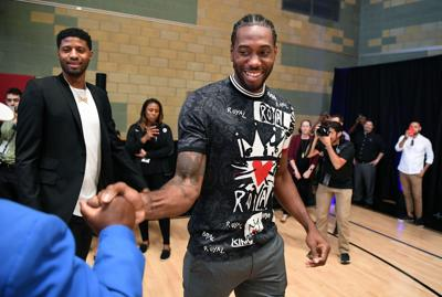 Newly-signed Los Angeles Clippers players Paul George, left, and Kawhi Leonard are greeted at Green Meadows Recreation Center before a news conference in Los Angeles on July 24, 2019.