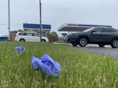 Gloves in grass at Marathon gas station, 3024 Rapids Drive