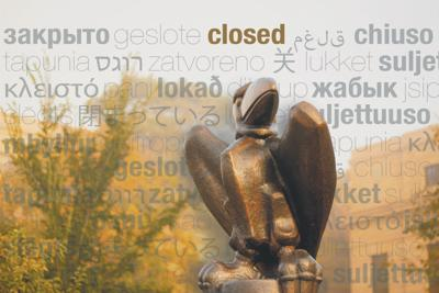 """The word """"closed"""" in various languages sets the backdrop behind the Jayhawk statue in front of Strong Hall."""