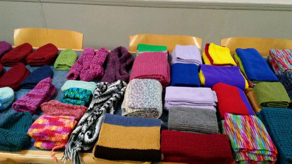 Folded scarves and hats cover a table