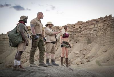 Kevin Hart, Dwayne Johnson, Jack Black and Karen Gillan stand in the desert in a shot from the movie Jumanji: The Next Level
