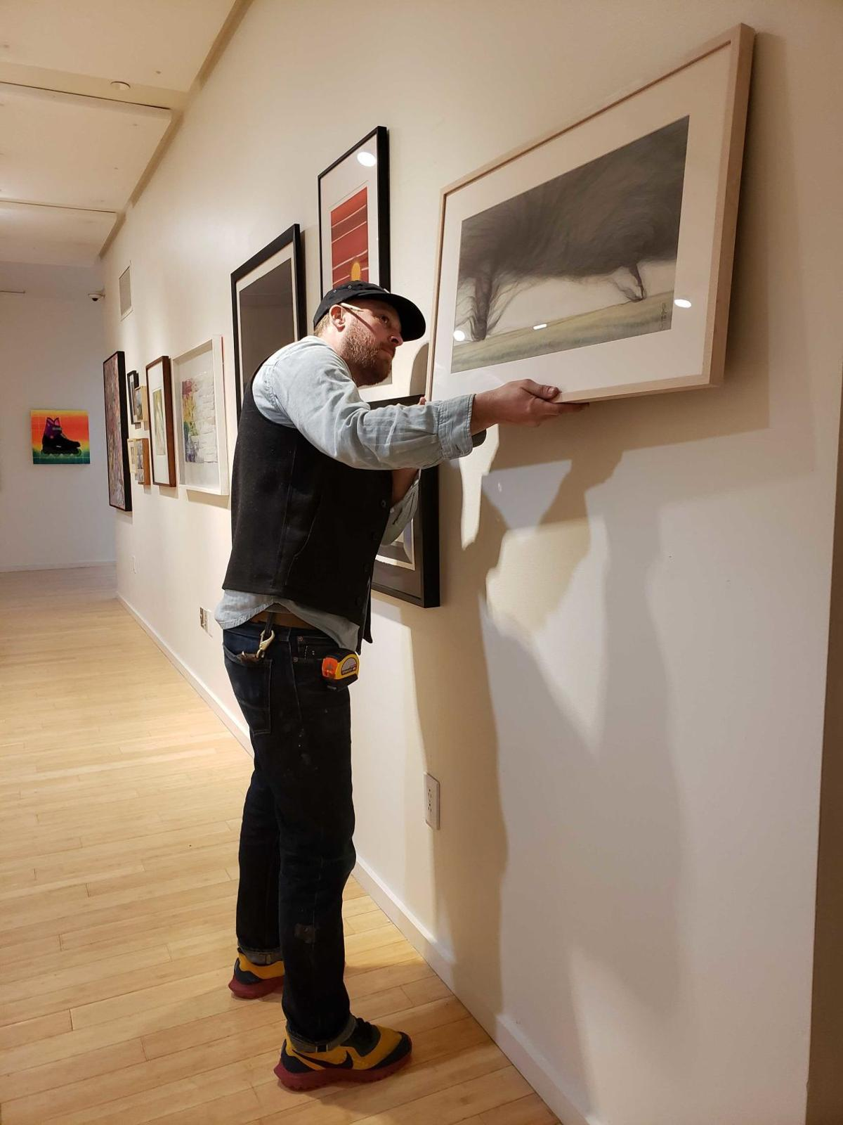 A man hangs a work of art on the wall of an exhibit