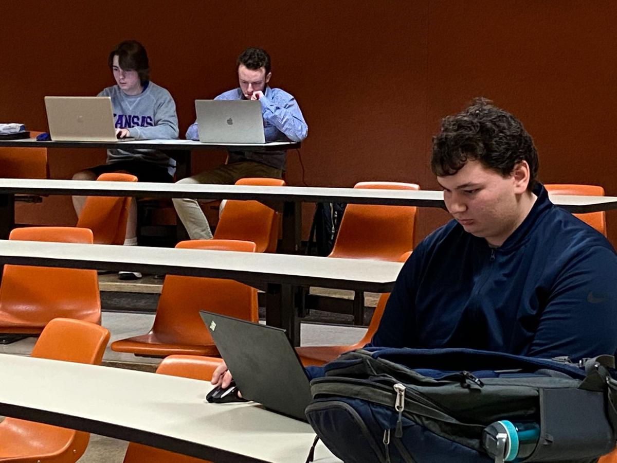 Three students work on their laptops in a lecture-style room. One student sits in the foreground and two others sit several rows behind him.