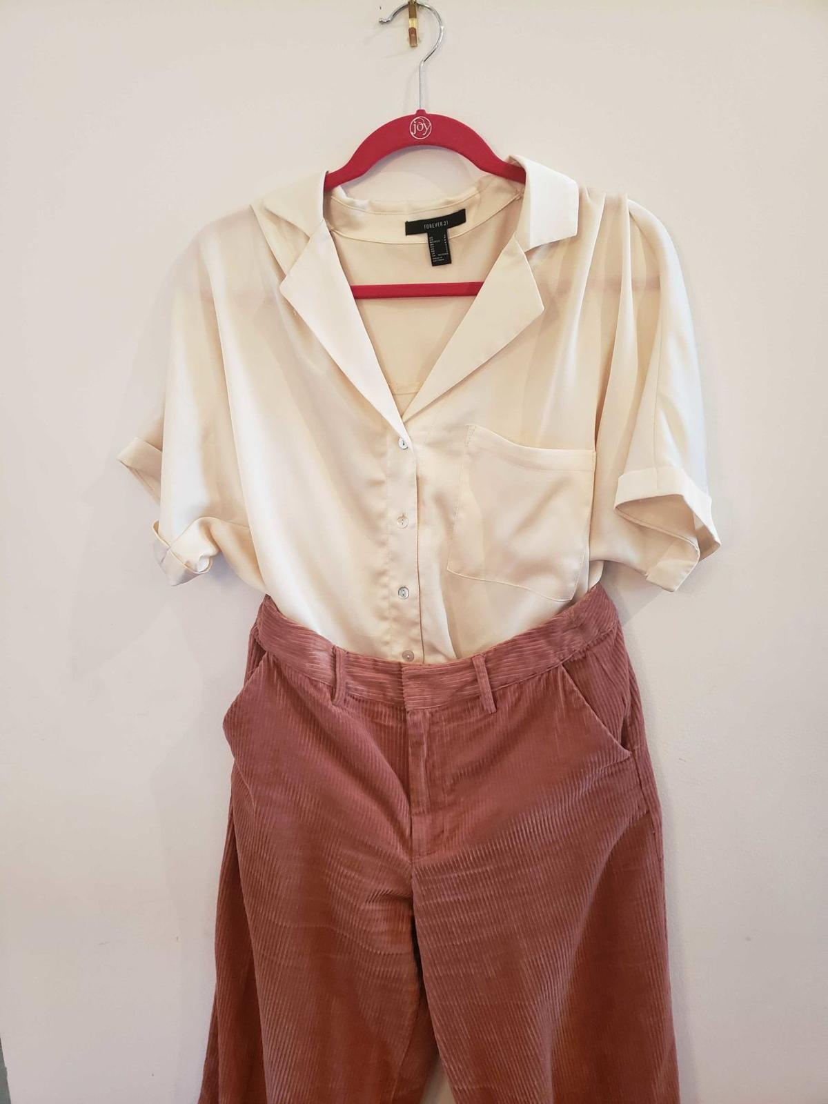 A short-sleeved blouse and corduroy pants hang on a hanger