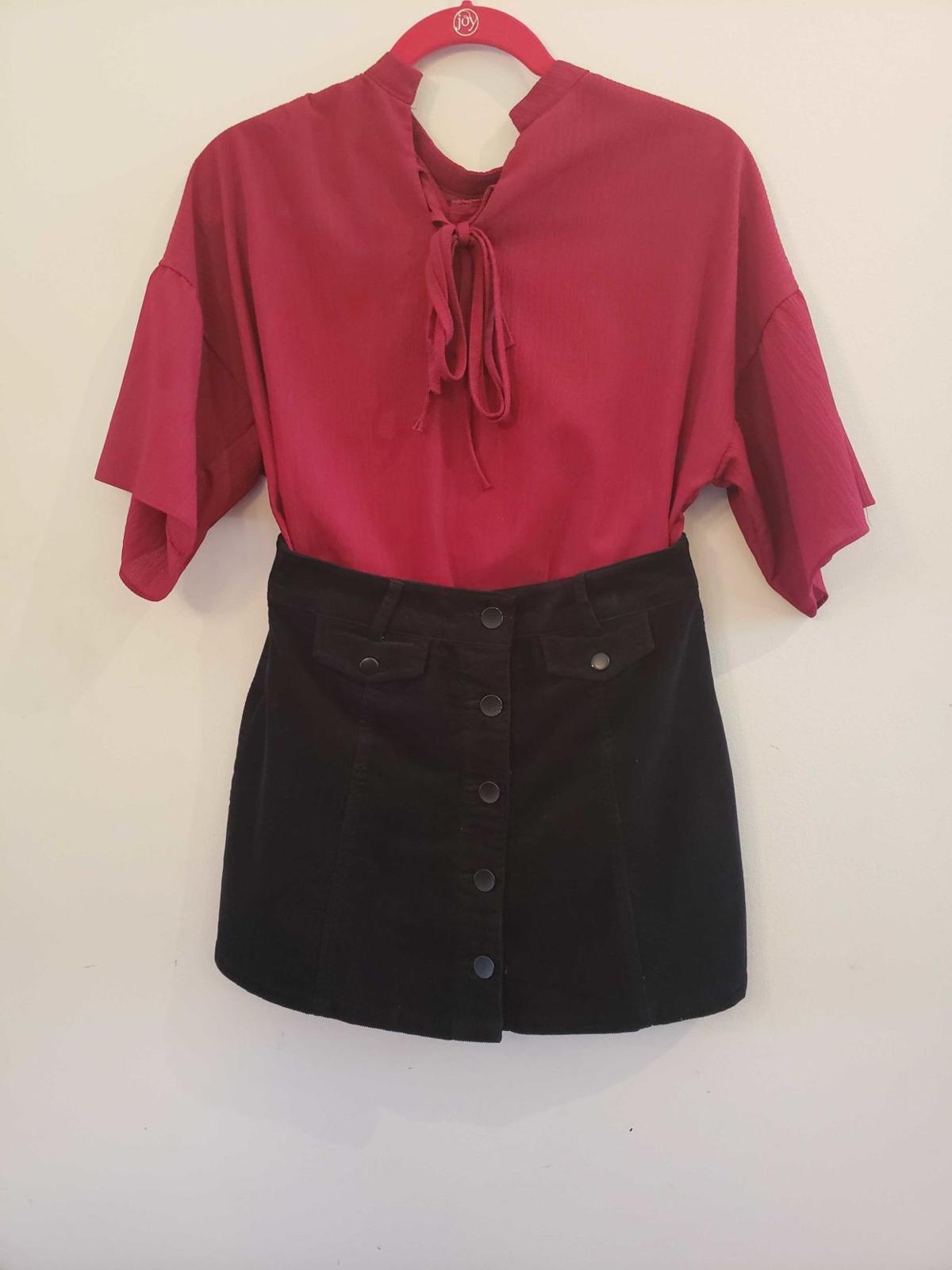 A tied blouse and corduroy skirt hang on display