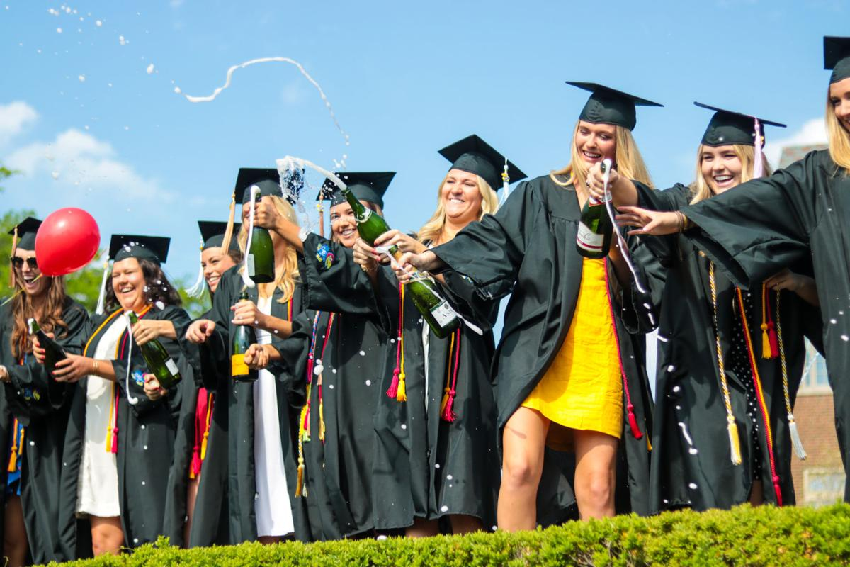 A group of graduates pop bottles of champagne while posing for photos at Commencement in 2018.